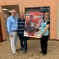 Glen Stucki  presenting his Spiderman painting to the Library Director